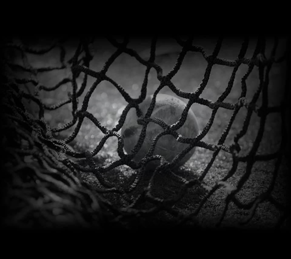 Black and white photo of a lacrosse ball in a net